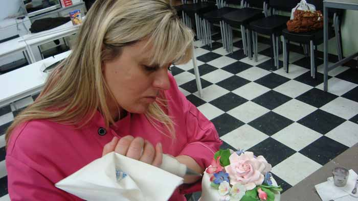 Woman putting flowers on cake