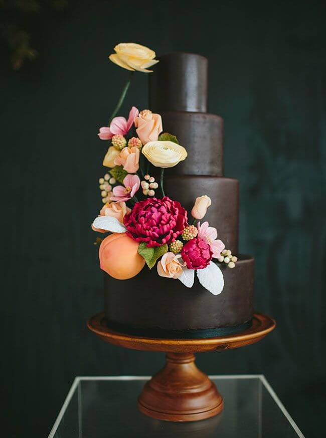 Dark wedding cake with colorful flowers