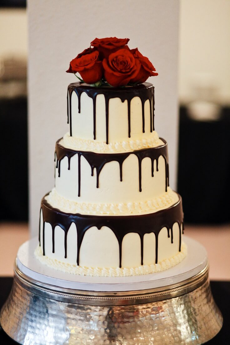 3-tiered white cake with red flowers on top and drips on sides