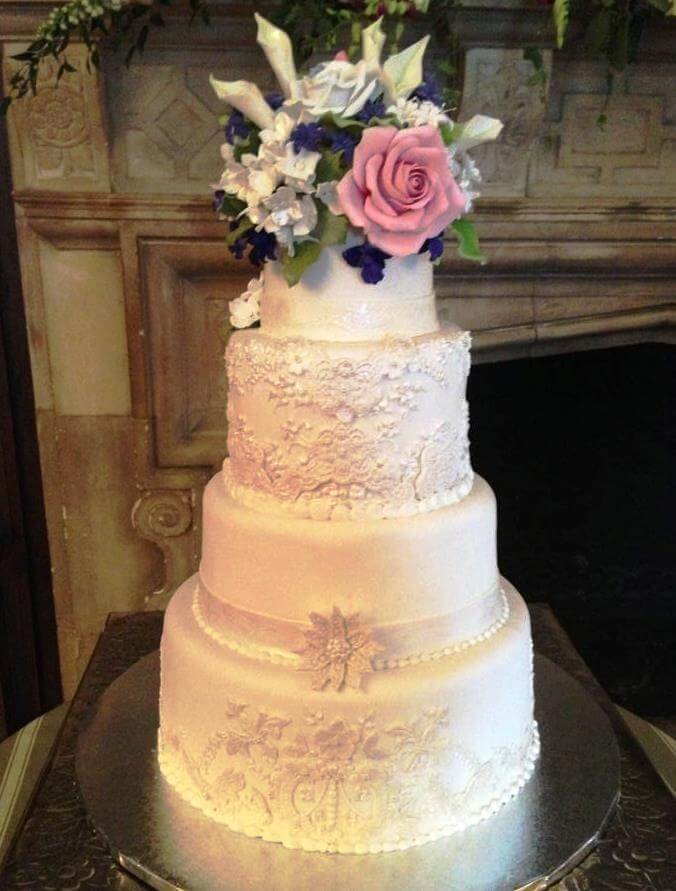 4-tiered cake with pink, white and purple flowers on top