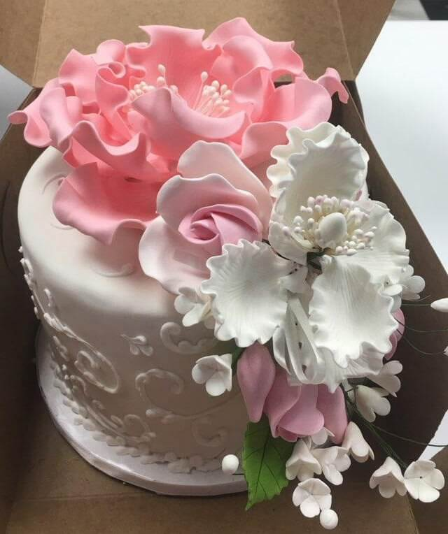 White cake with white and pink flowers