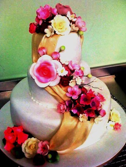 """3-tiered cake with """"sash"""" and pink flowers"""