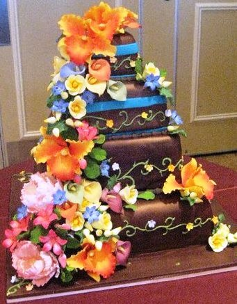 brown 4-tiered cake with colorful flowers