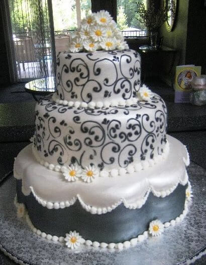 White and grey 3-tiered cake with daisies
