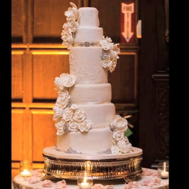 6-tiered white cake with white flowers