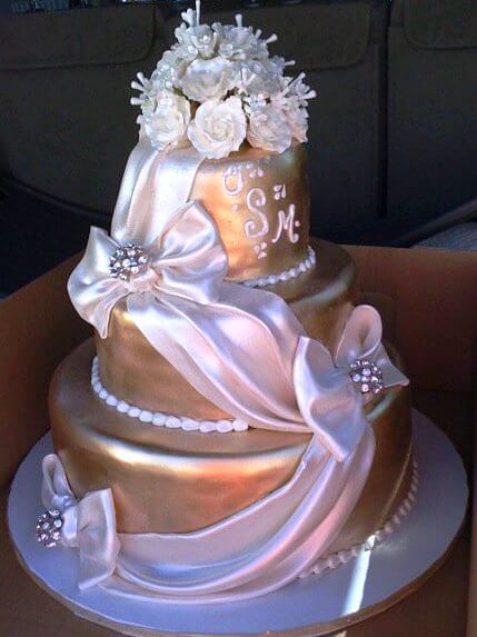 3-tiered gold cake with ribbon and white flowers