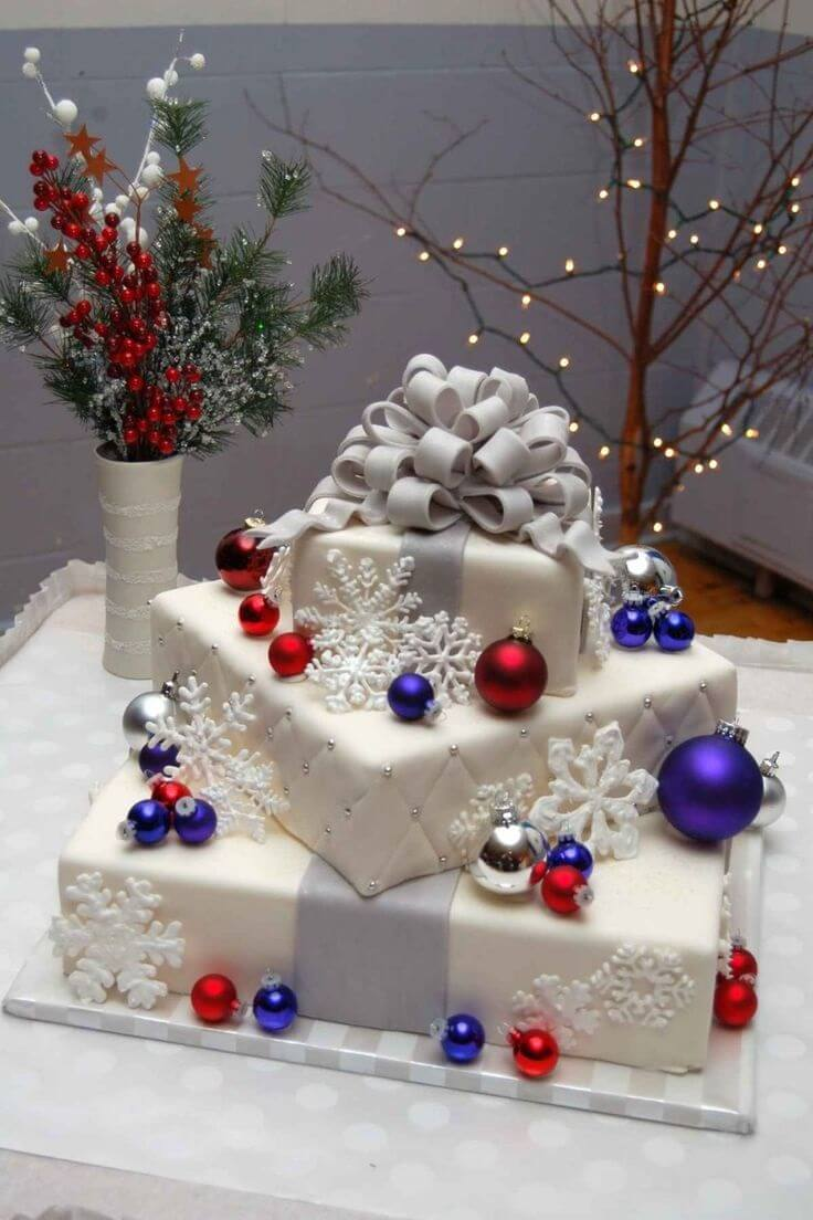 3-tiered white cake wrapped like present with ornaments