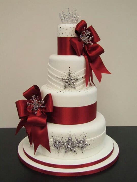 4-tiered white and red cake with tiara on top