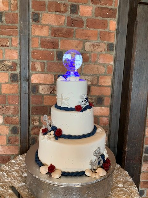 white 3-tiered cake with anchors