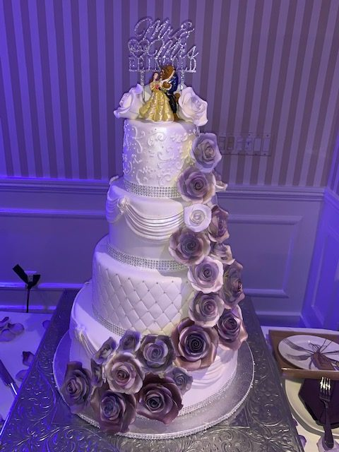 White 4-tiered wedding cake with purple flowers