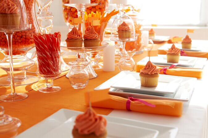 Table setting with orange cupcakes