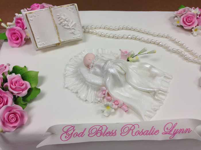 White cake with pink flowers and baby