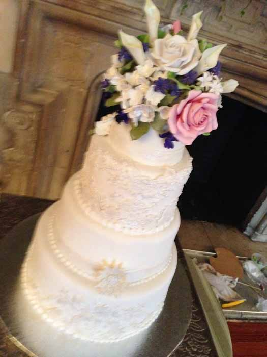 4-tiered angled picture of white cake with pink, white and purple flowers on top