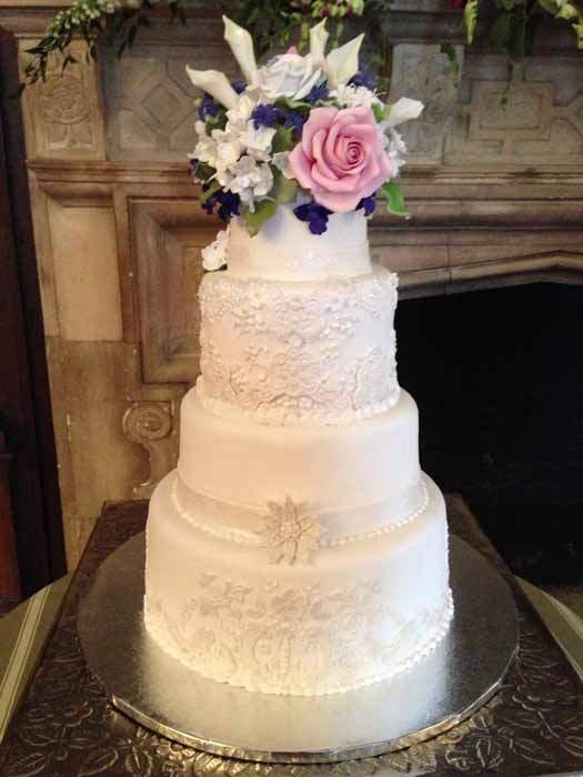 4-tiered white cake with pink, white and purple flowers on top
