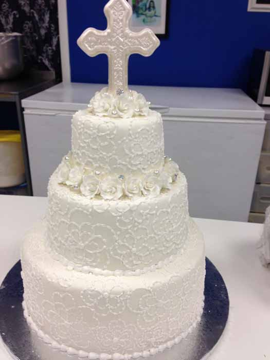 3-tiered all white cake with cross on top