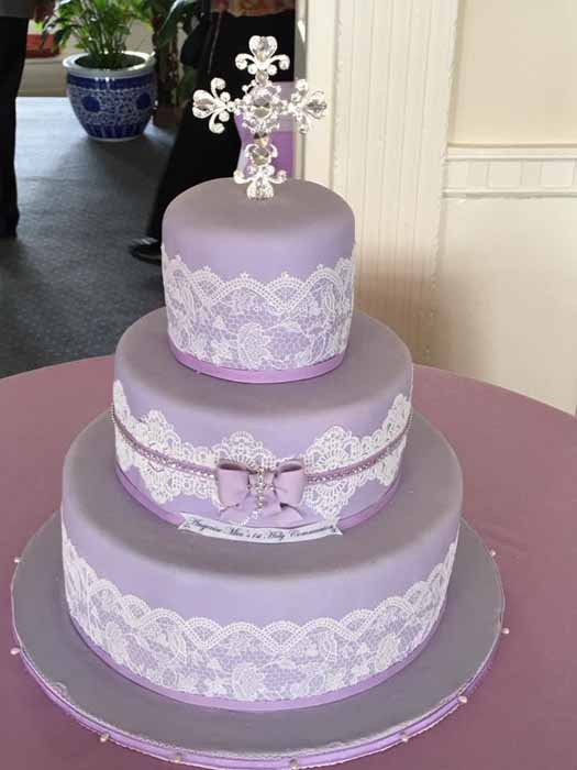 purple and lace 3-tiered cake with cross on top