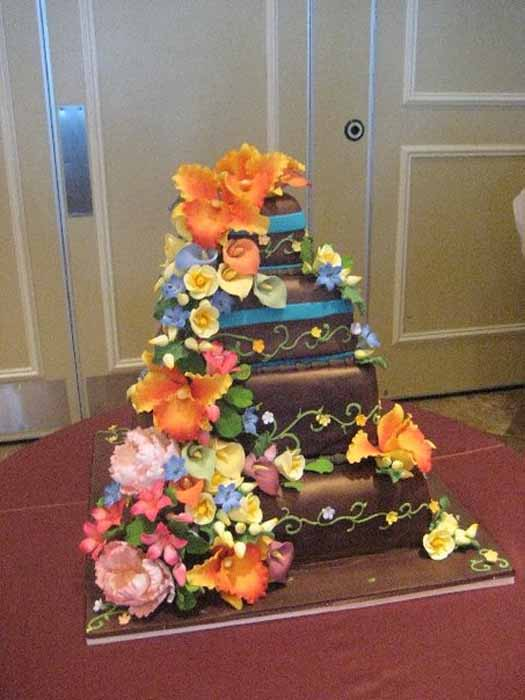 Cake with colorful flowers cascading down side of it