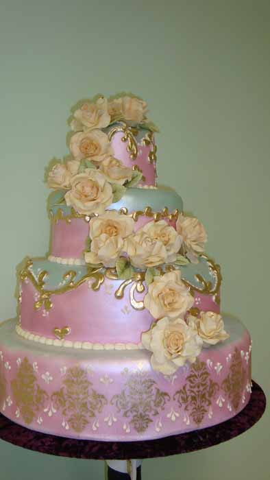 pink 4-tiered cake with off white flowers