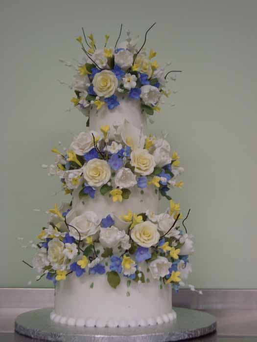 3 tiered cake with blue, yellow and white flowers