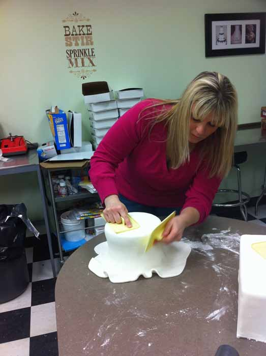 Woman putting fondant on cake